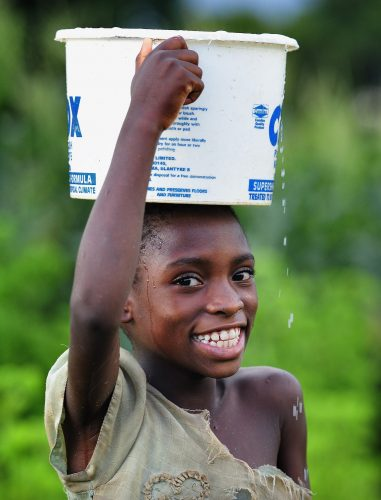 A girl carries a bucket of water on her head in Karonga, a town in northern Malawi where the ACT Alliance worked with local residents to recover from a 2009 earthquake.